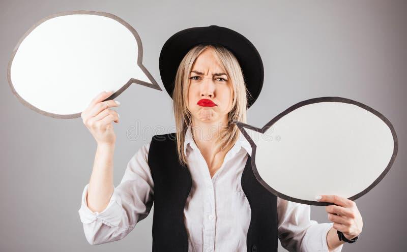 Annoyed不满意拿着交谈讲话bubles的黑帽会议的滑稽的妇女 免版税图库摄影