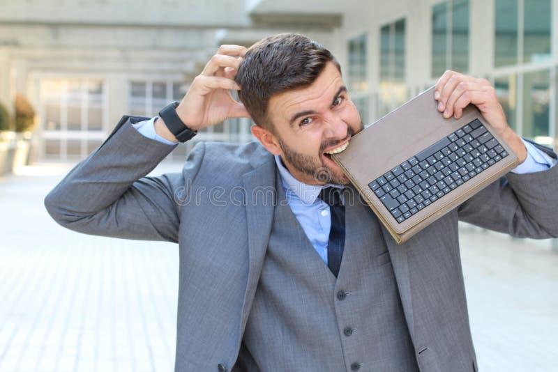 Annoyed运作bitting他的膝上型计算机 图库摄影