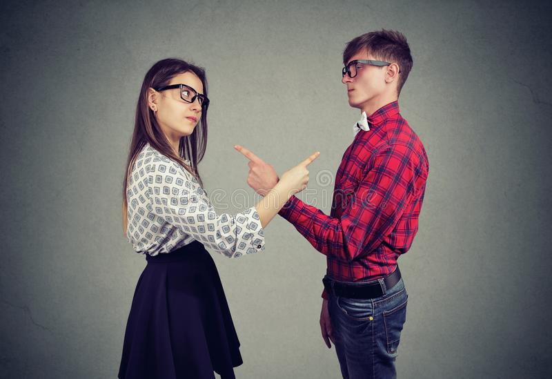Annoyed angry man and woman facing relationships problems, pointing fingers each other blaming for mistakes royalty free stock photos
