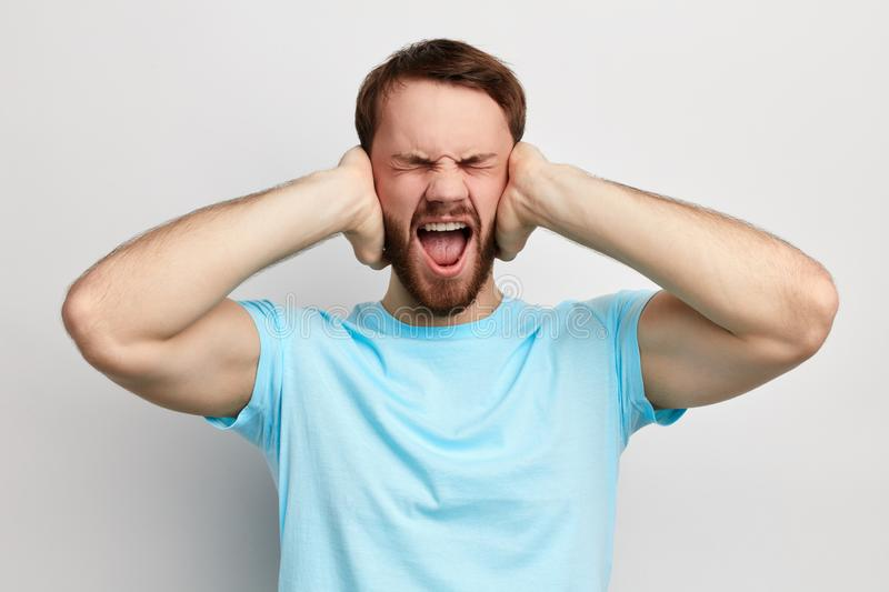 Annoyed angry young emotional man plugging ears with hands stock photo