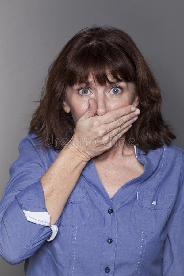 Mature woman looking shocked against white stock photo
