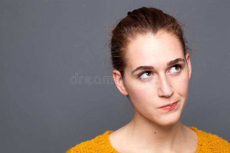 Annoyed beautiful girl looking up, observing emotions of doubt, closeup royalty free stock image