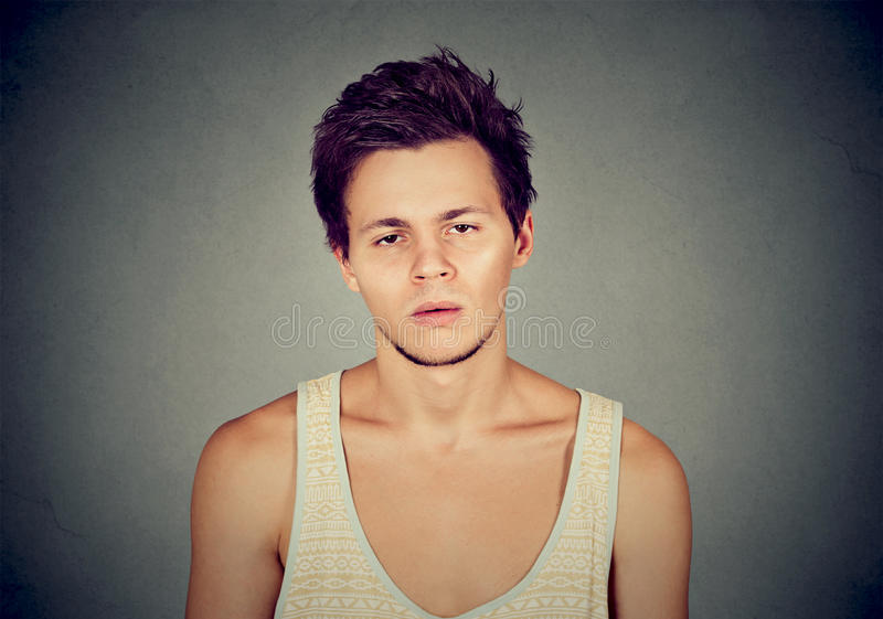 Annoyed bored young man looking at camera stock images