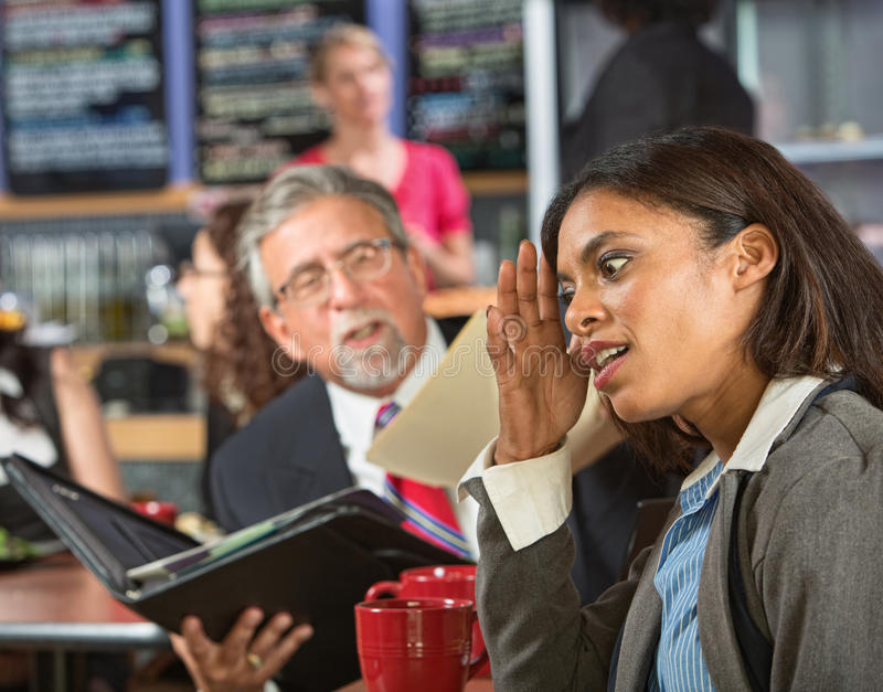 Annoyed with Boss at Lunch. Bored business women with executive reading during lunch stock image