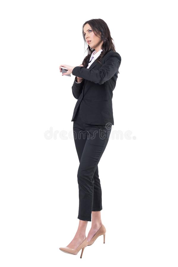 Annoyed business woman checking time holding cellphone waiting for someone stock photos