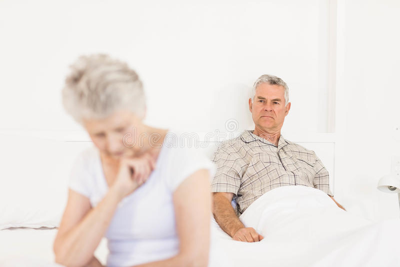 Annoyed couple ignoring each other. In the bedroom stock image