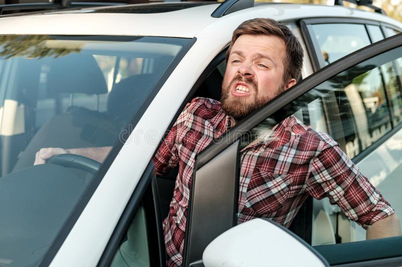 An annoyed driver opened the door of his car and screams furiously at someone. Close-up royalty free stock photo