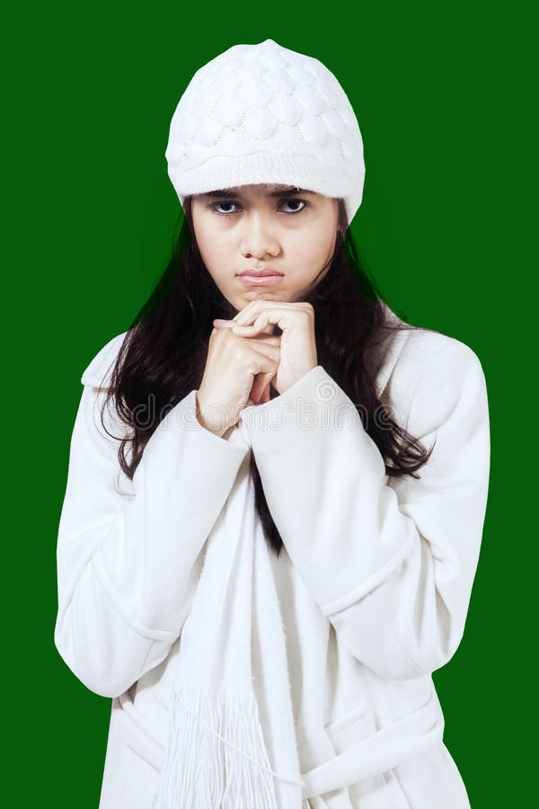 Annoyed girl in winter coat. Portrait of young annoyed woman wearing winter coat and hat, shot in studio against green background royalty free stock photo