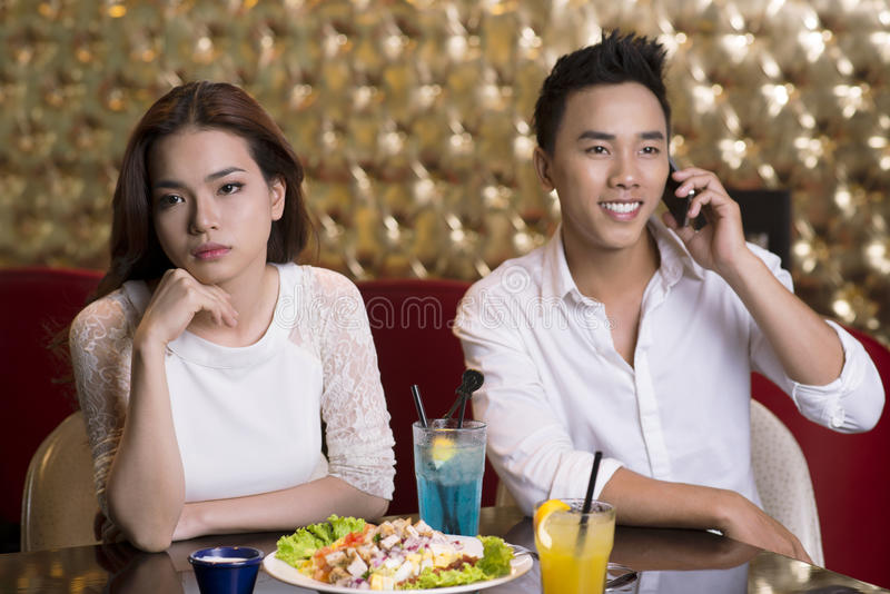 Annoyed girlfriend. Lovely lady being annoyed with her boyfriend talking on the phone in the middle of the date stock photo