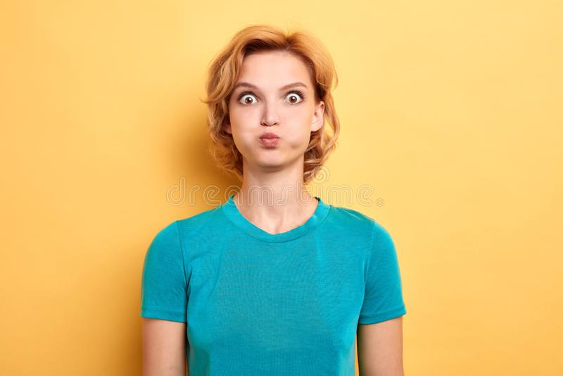 Annoyed a irrité la jeune femme soufflant ses joues image stock