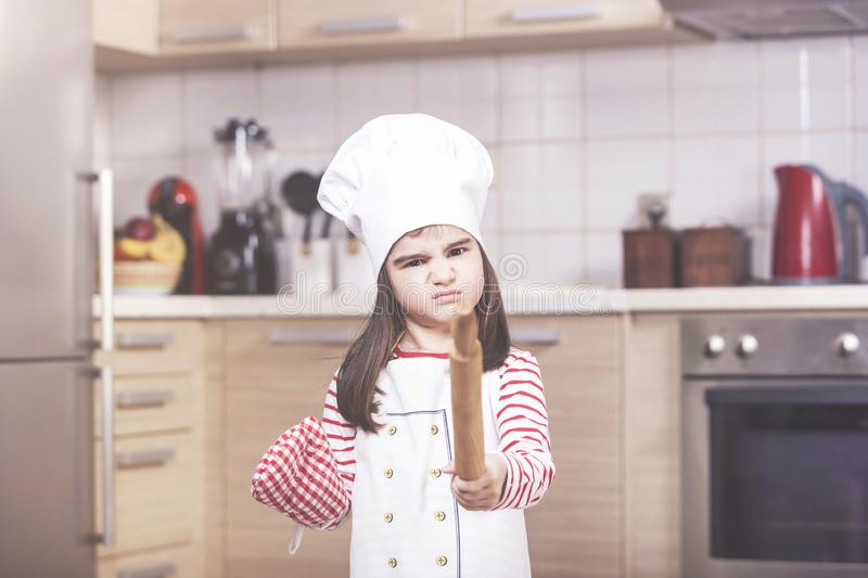 Annoyed little girl chef royalty free stock photo