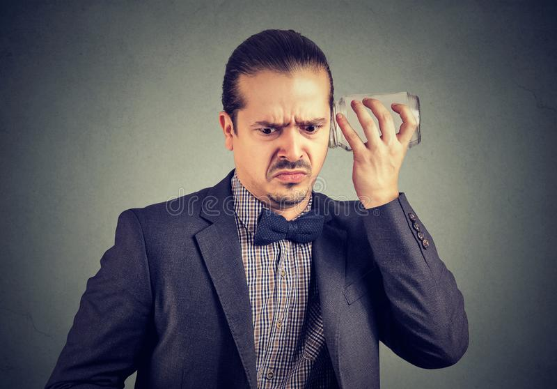 Annoyed man eavesdropping with glass jar. Upset man in looking displeased while listening to rumors with glass jar on gray background stock photography