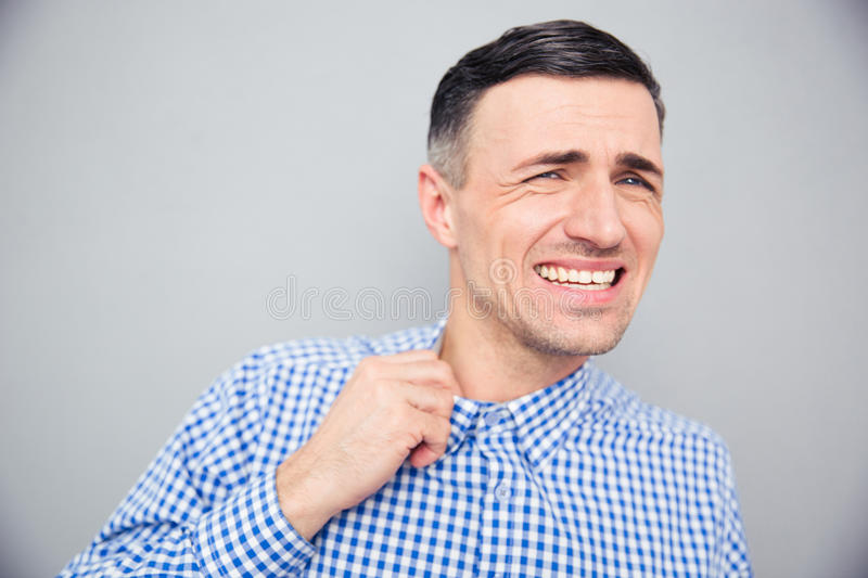 Annoyed man loosing his shirt to relax a bit after hard work. Over gray background stock photography