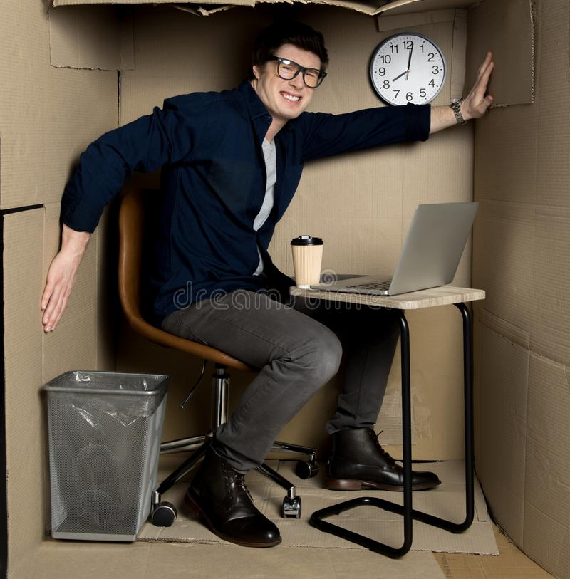 Annoyed manager is feeling discomfort inside small carton room. Overcrowding concept. Full length portrait of angry young employee is sitting in confined carton stock photos