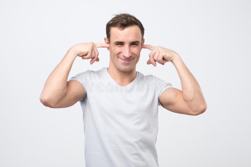 Annoyed mature italian man plugging ears with fingers. I do not want to listen to your excuses royalty free stock photos