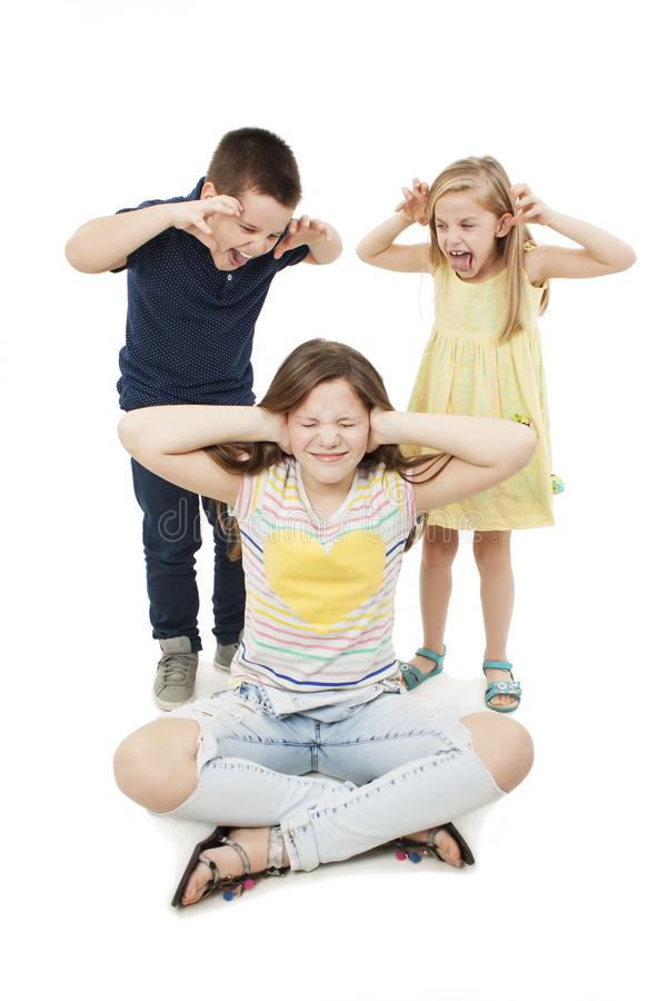 Annoyed old sister. Teenage girl covering her ears with her hands, young brother and sister screaming in her ears stock images