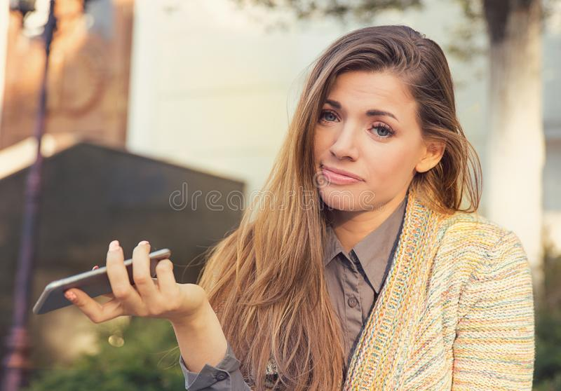 Annoyed sad woman with mobile phone standing outside in the street stock photography