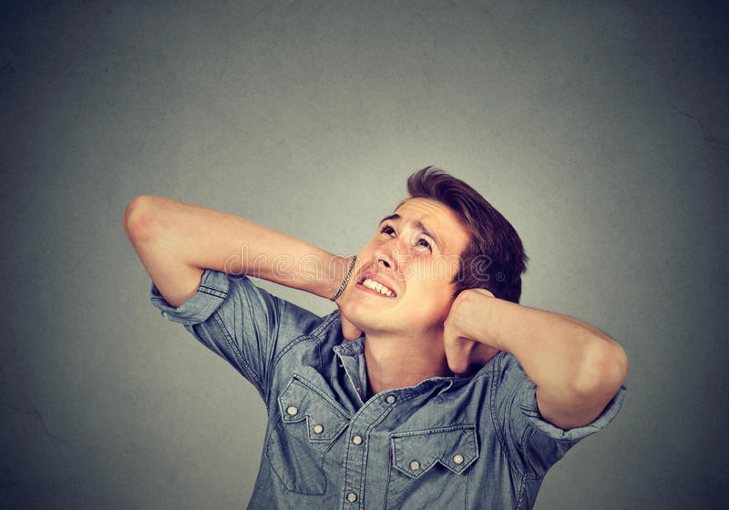 Annoyed stressed man covering his ears looking up stock image
