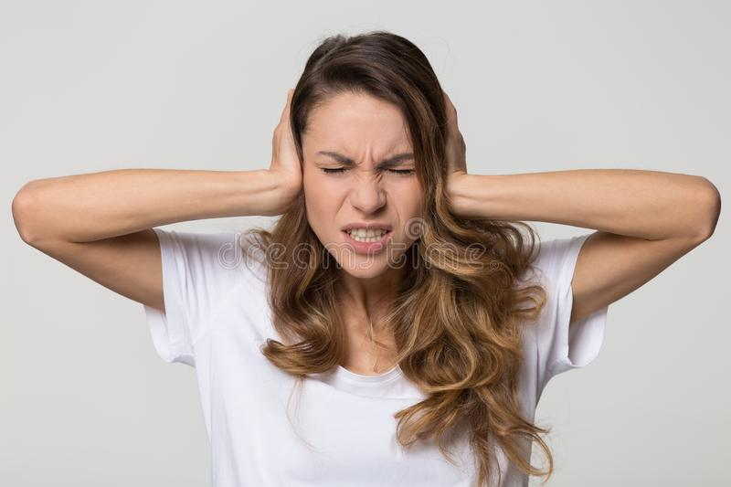 Annoyed stressed woman covering ears with hands feeling ear pain. Annoyed stressed woman cover ears feel hurt ear ache pain otitis suffer from loud noise sound stock photography