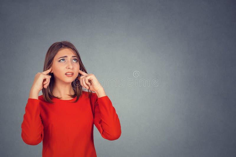 Annoyed subrayó a la mujer que cubría sus oídos, mirando para arriba fotos de archivo