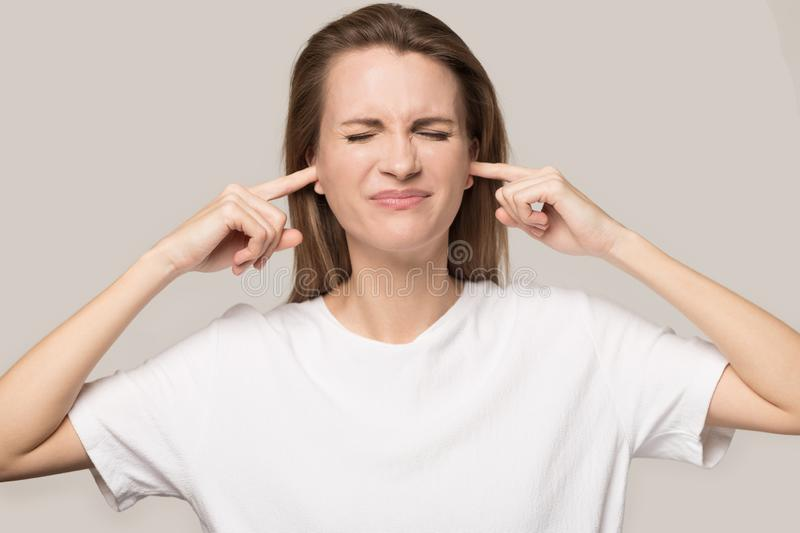 Annoyed unhappy woman plug ears with fingers, avoid loud noise royalty free stock photos