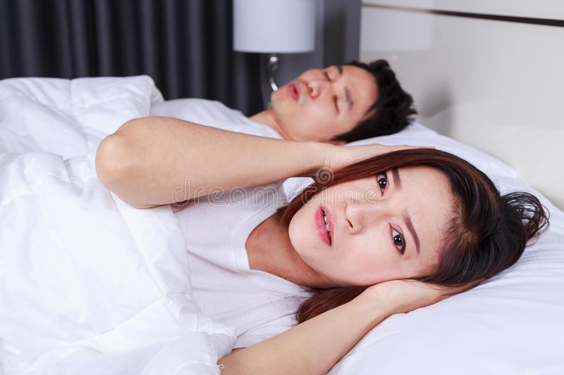 Annoyed wife blocking her ears from noise of husband snoring in stock image