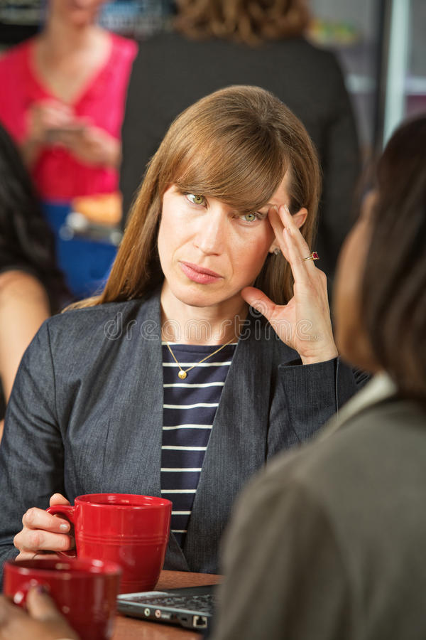 Annoyed Woman on Break. Annoyed business women with coffee talking with coworker stock photo