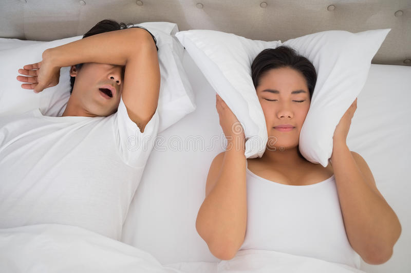 Annoyed woman covering her ears with pillows to block out snoring royalty free stock images