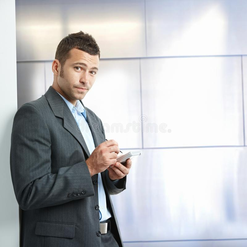 Annoyed young businessman in suit with tablet. Annoyed young caucasian businessman in suit with tablet, standing in front of wall at business office. Looking at stock images