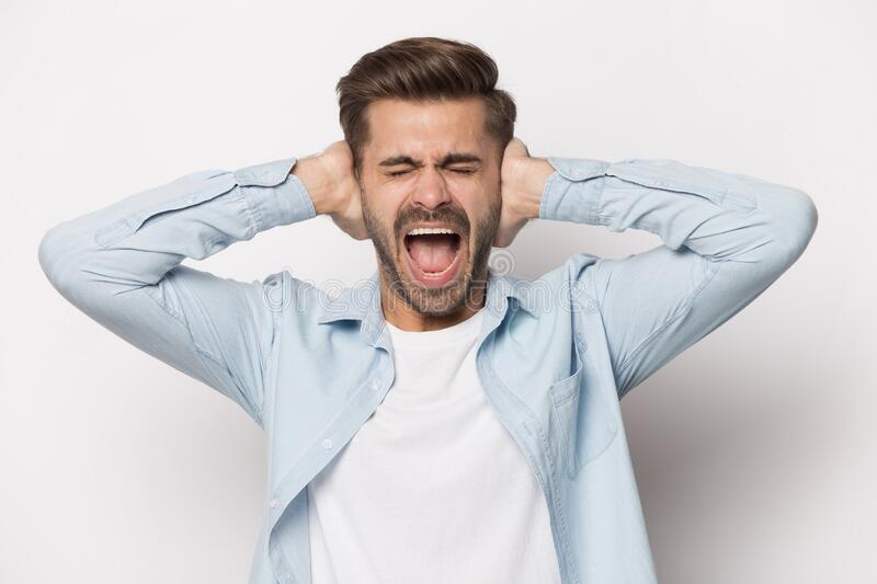 Annoyed young man covering ears with hands shouting, refusing listening. royalty free stock photo