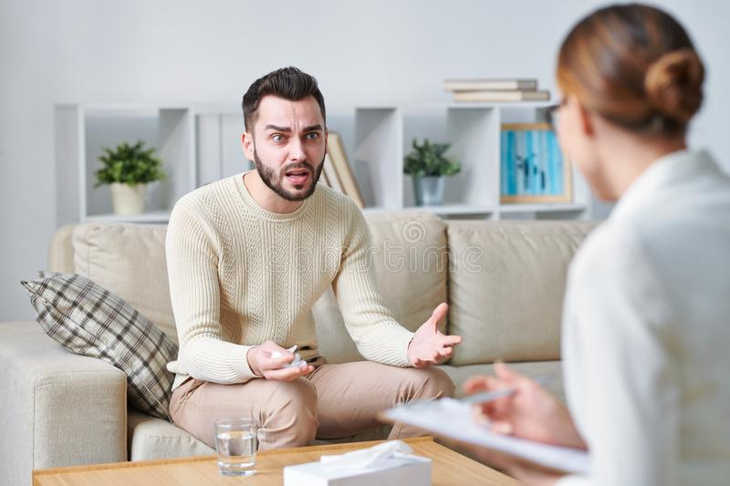 Irritation. Annoyed young men in casualwear sitting on couch and expressing displeasure while explaining his problem to counselor royalty free stock photo