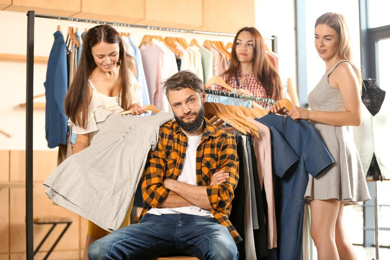 Annoyed young man waiting for his girlfriend and her friends while they choosing clothes in shop royalty free stock photos