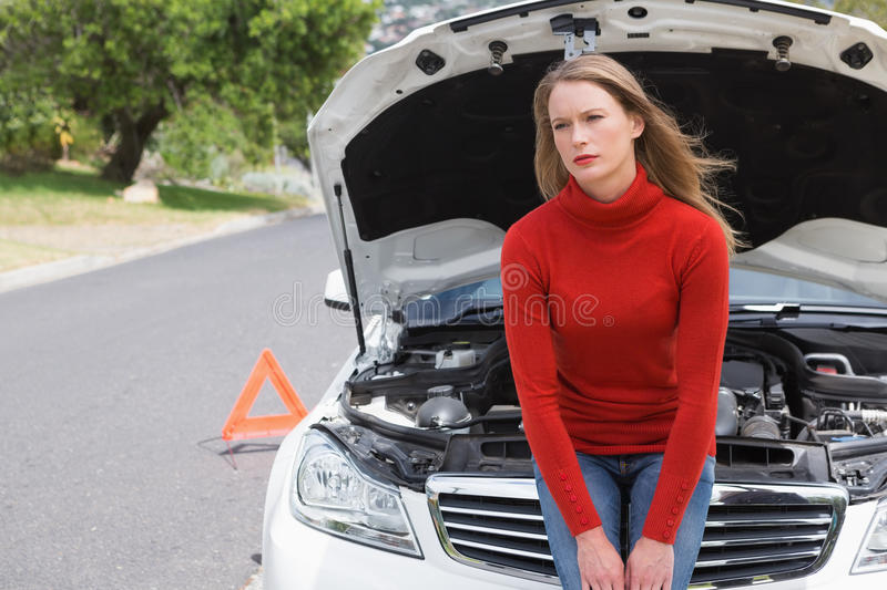 Annoyed young woman beside her broken down car. In the street royalty free stock image