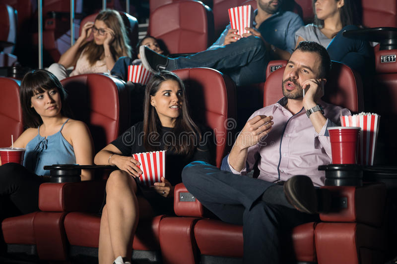 Annoying man at the movie theater. Hispanic men being disrespectful by talking on the phone at the movie theater next to some annoyed neighbors royalty free stock images