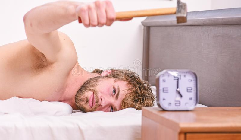 Annoying sound. Annoying ringing alarm clock. Man bearded annoyed sleepy face lay pillow near alarm clock. Guy knocking. With hammer alarm clock ringing. Break stock images