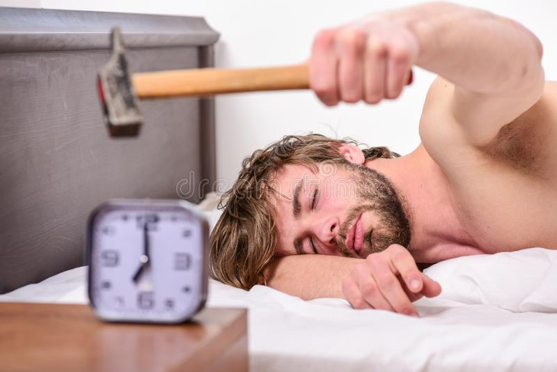Annoying sound. Stop ringing. Annoying ringing alarm clock. Man bearded annoyed sleepy face lay pillow near alarm clock. Guy knocking with hammer alarm clock royalty free stock photo
