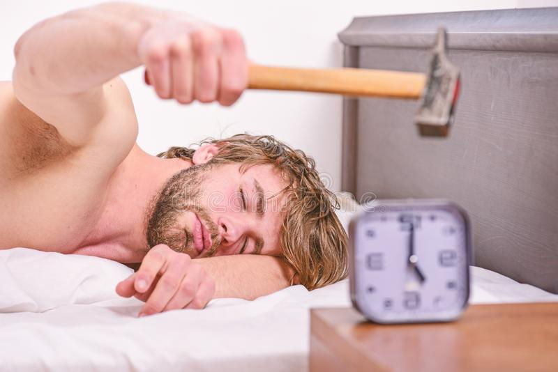 Annoying sound. Stop ringing. Annoying ringing alarm clock. Man bearded annoyed sleepy face lay pillow near alarm clock. Guy knocking with hammer alarm clock stock photography