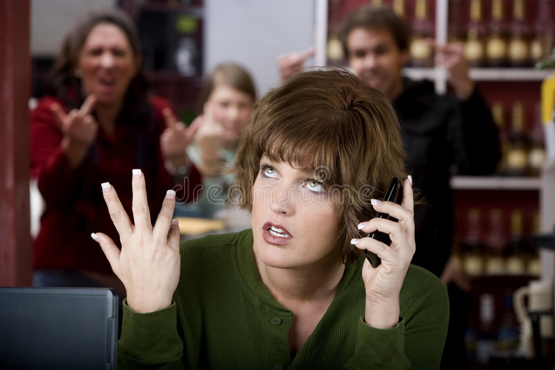 Annoying woman on her cell phone. Annoying woman in a cafe on her cell phone gets the finger royalty free stock image