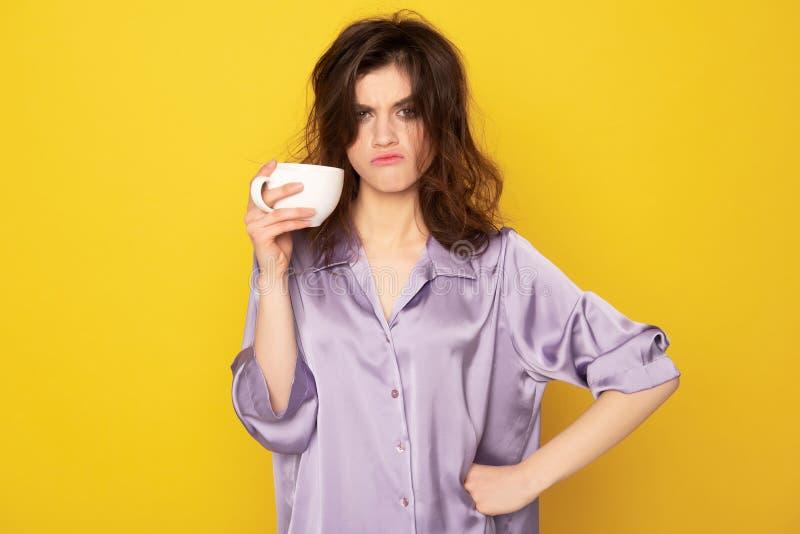 Annoyingly se unga flickan med koppen kaffe arkivfoton