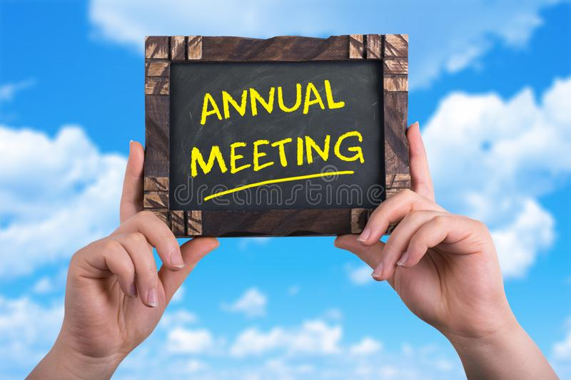 Annual meeting. A woman holding chalkboard with words annual meeting on blue sky background royalty free stock photos