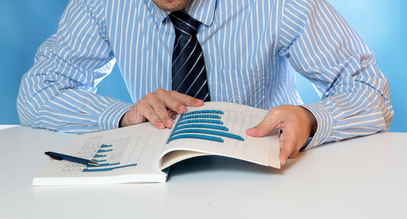 Annual report. Businessman working analyzing a annual report royalty free stock photo