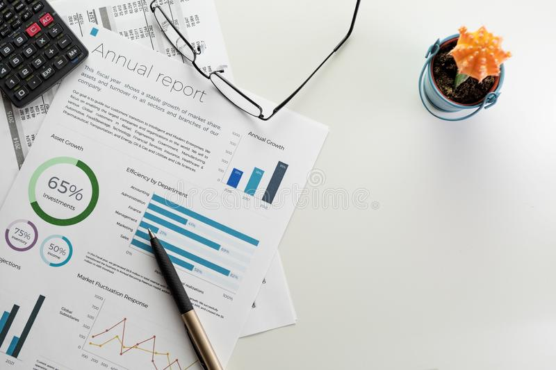 Annual report sheet with charts, pen, calculator, eyeglasses and cactus on white royalty free stock photos
