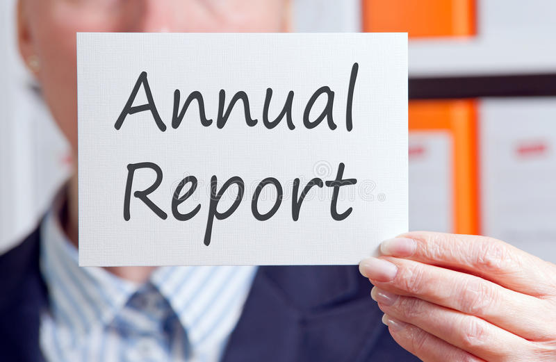 Annual Report. Text 'Annual Report' written on a white card in black ink and held in the hand of a businesswoman, office background stock images