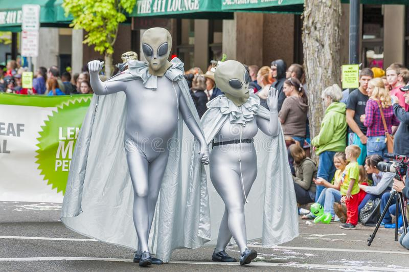Annual UFO Festival in McMinnville Oregon. McMinnville, Oregon, USA - May 16, 2015: A couple wearing silver alien costumes walk down McMinnville Oregon`s main stock photos