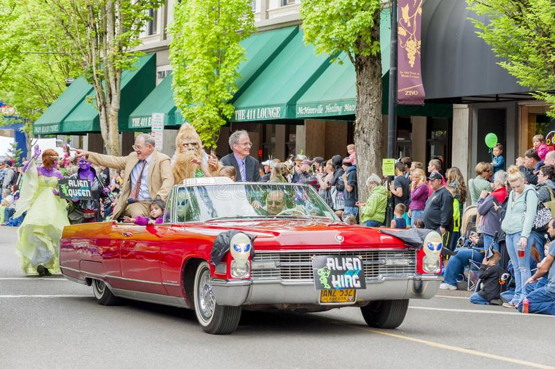 Annual UFO Festival in McMinnville Oregon. McMinnville, Oregon, USA - May 16, 2015: Alien King rides in a red cadillac while the alien Queen walks behind in the royalty free stock photography