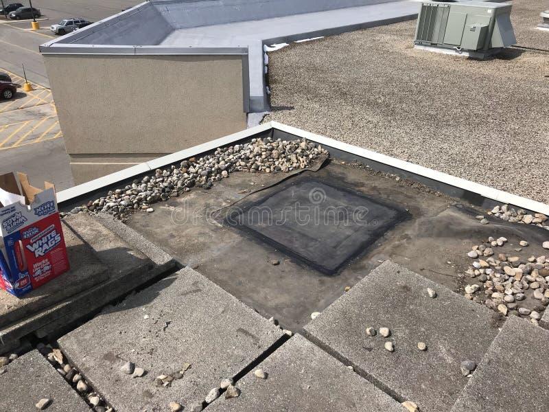 Annullierung einer Entlüftung; Dach-Reparaturen auf Werbung mit Ballast beladenem EPDM-Dach; Flachdach lizenzfreie stockbilder