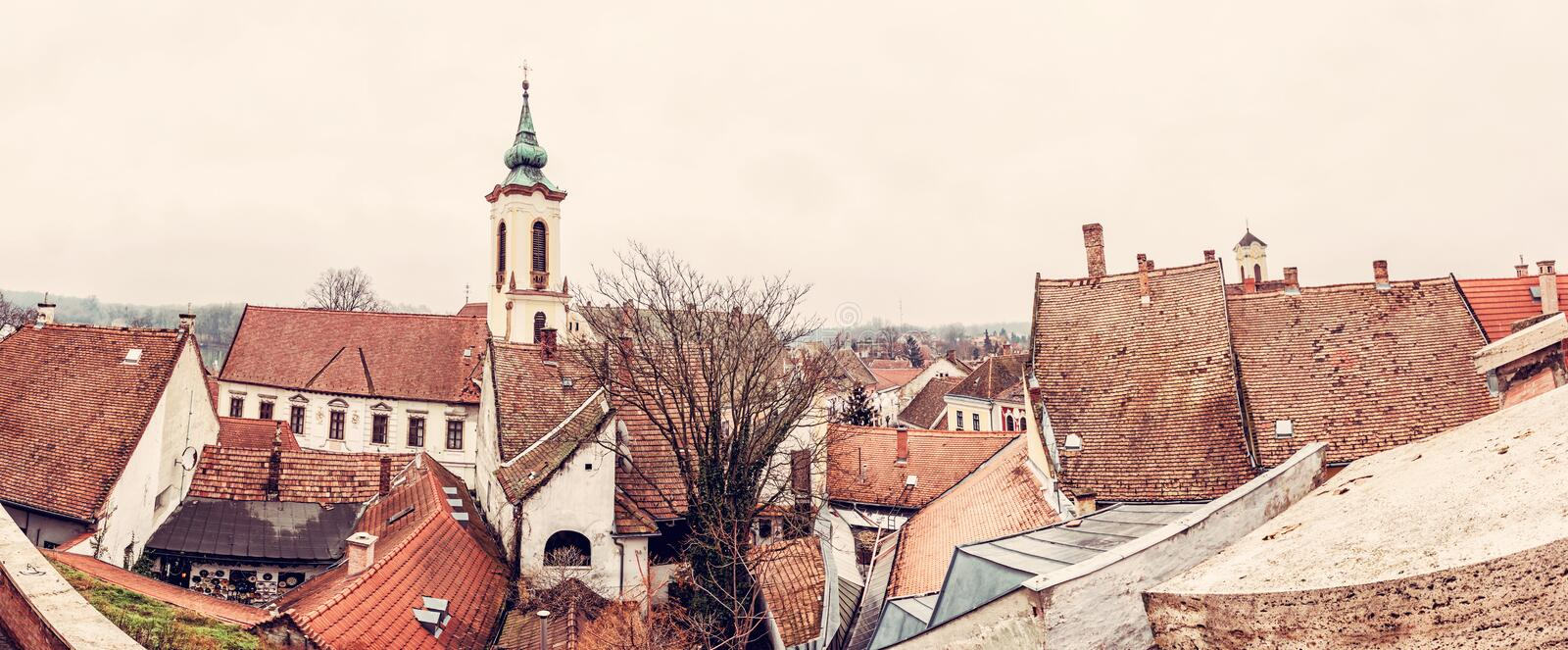 Annunciation church and red roofs of old houses, Szentendre. Hungary. Religious architecture. Panoramic scene. Place of worship. Red photo filter royalty free stock photo