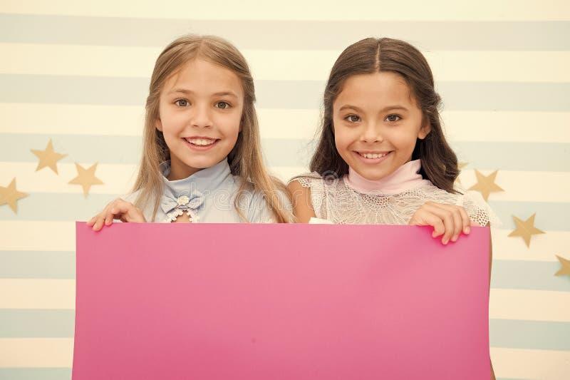 Annuncio della scuola per i bambini La vostra pubblicit? qui le piccole ragazze scherza la tenuta della carta rosa per l'annuncio immagine stock libera da diritti