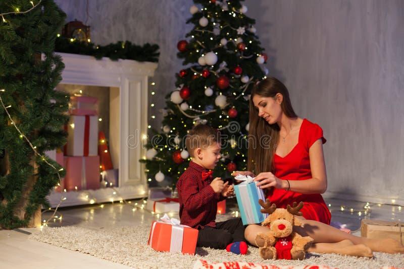 Ano novo aberto de árvore de Natal dos presentes da mãe e do rapaz pequeno fotos de stock