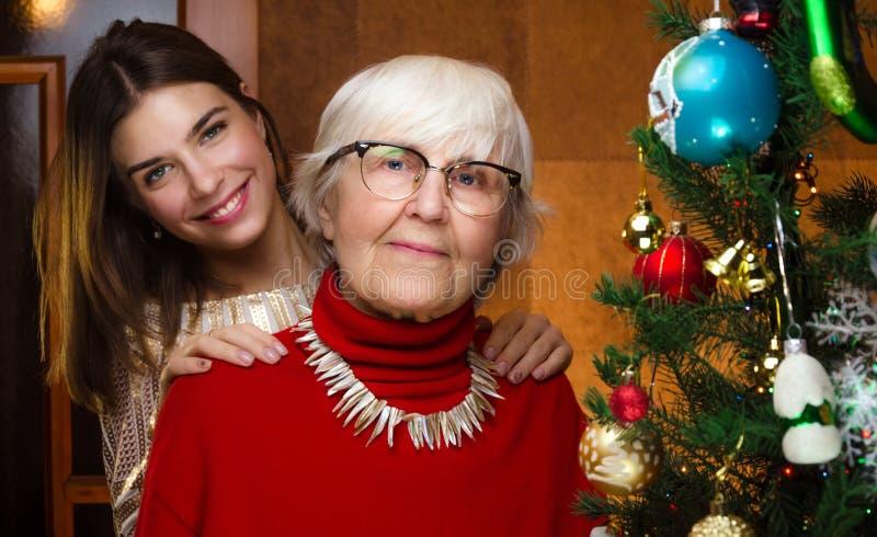 Ano novo avó superior e mulher caucasiano nova, adolescente perto da árvore de Natal a neta, aperto adolescente, abraça foto de stock